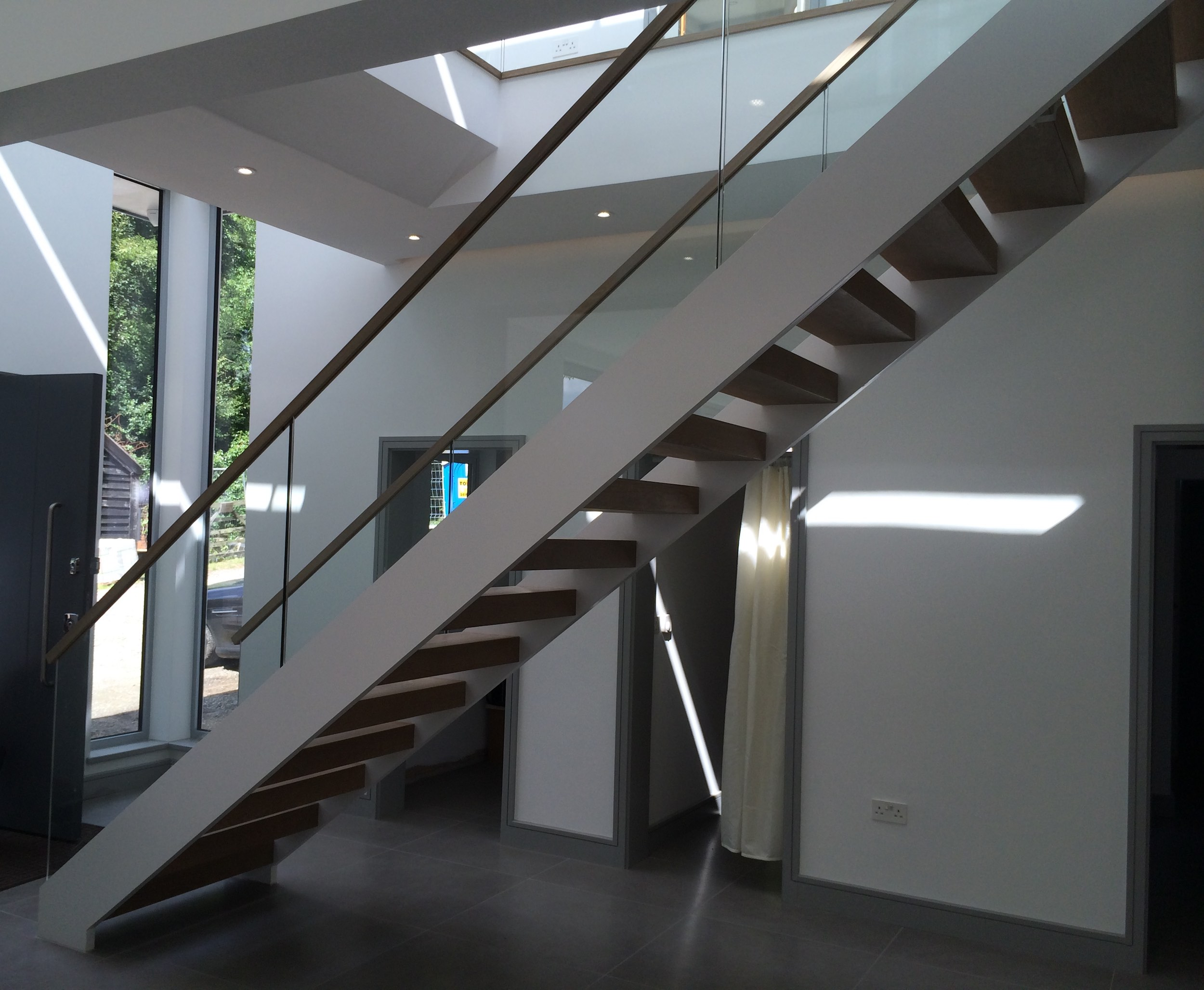 Steel stairs with wooden railing, glass balustrade, open risers and timber treads