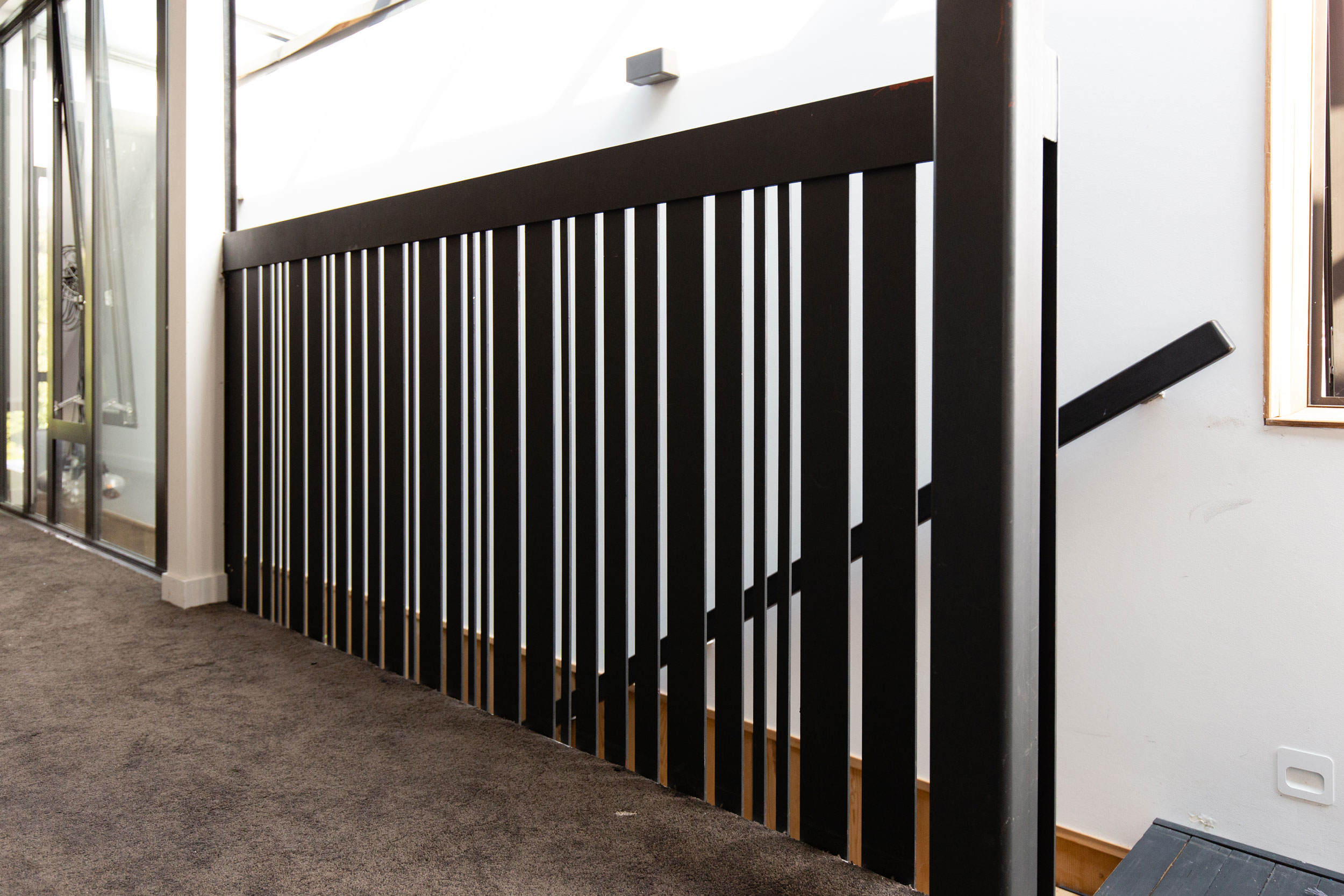 Slotted metal balustrade designed by Stairworks at the top of a staircase.