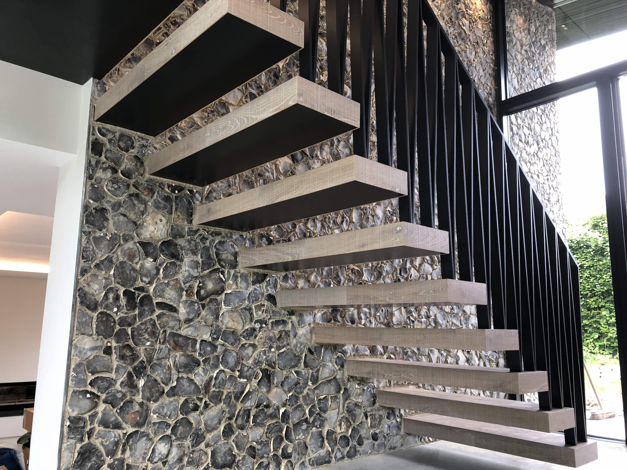 Floating staircase with metal balustrade and timber treads in farmhouse