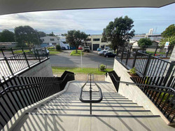 Concrete staircase with metal balustrades outside apartment entry in Auckland