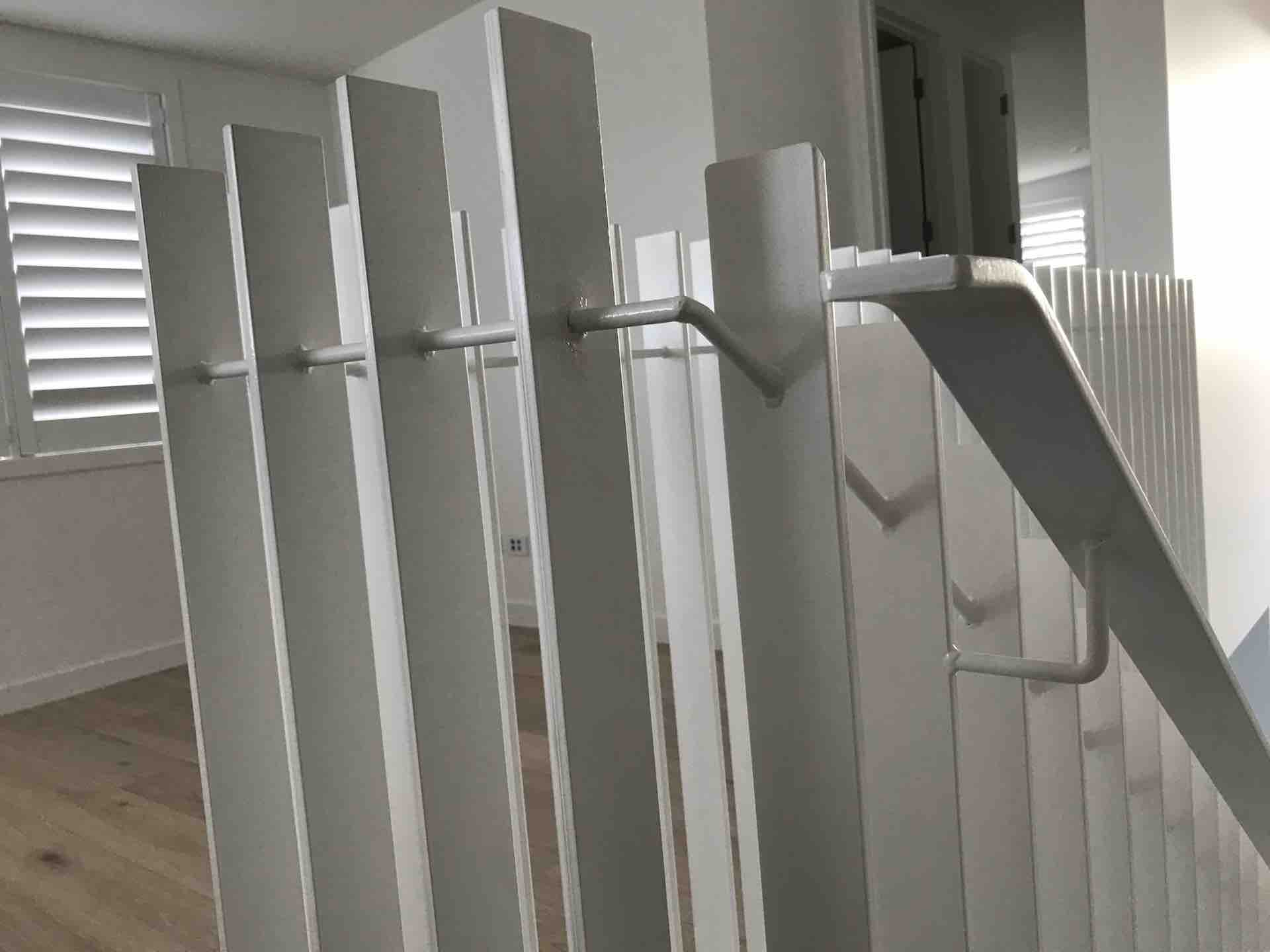 Flat steel welded to create white balustrade for staircase
