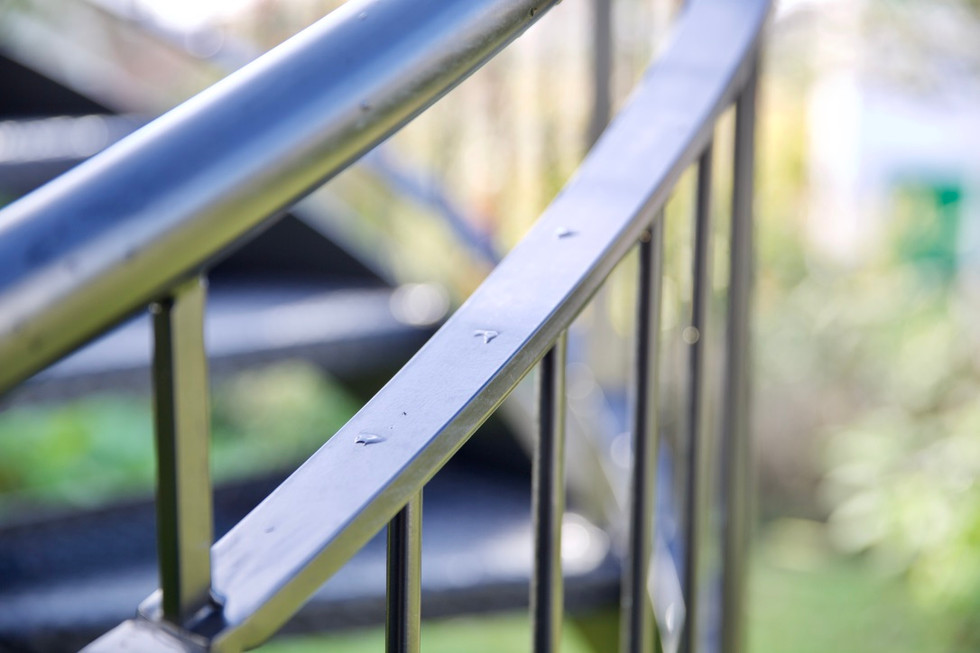 Steel spiral staircase with metal balustrade and handrail, metal treads and open risers.