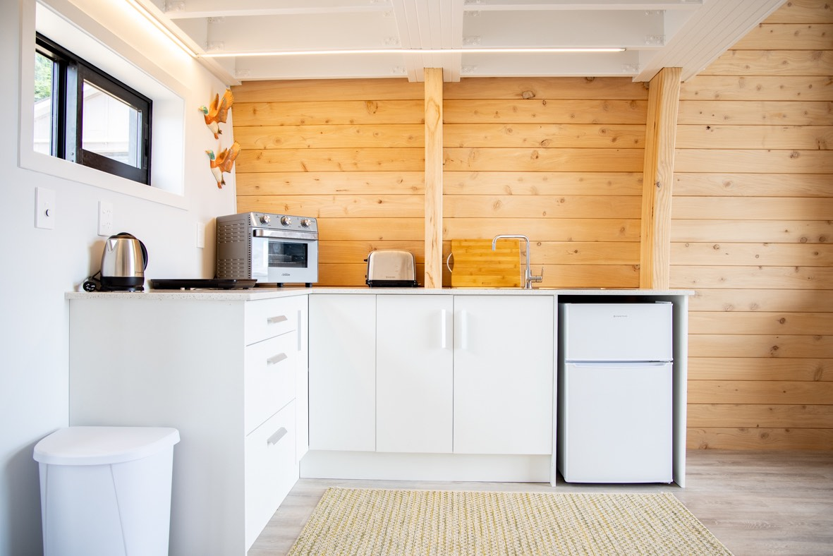 Space saving stairs allow for larger kitchen in tiny home in New Zealand