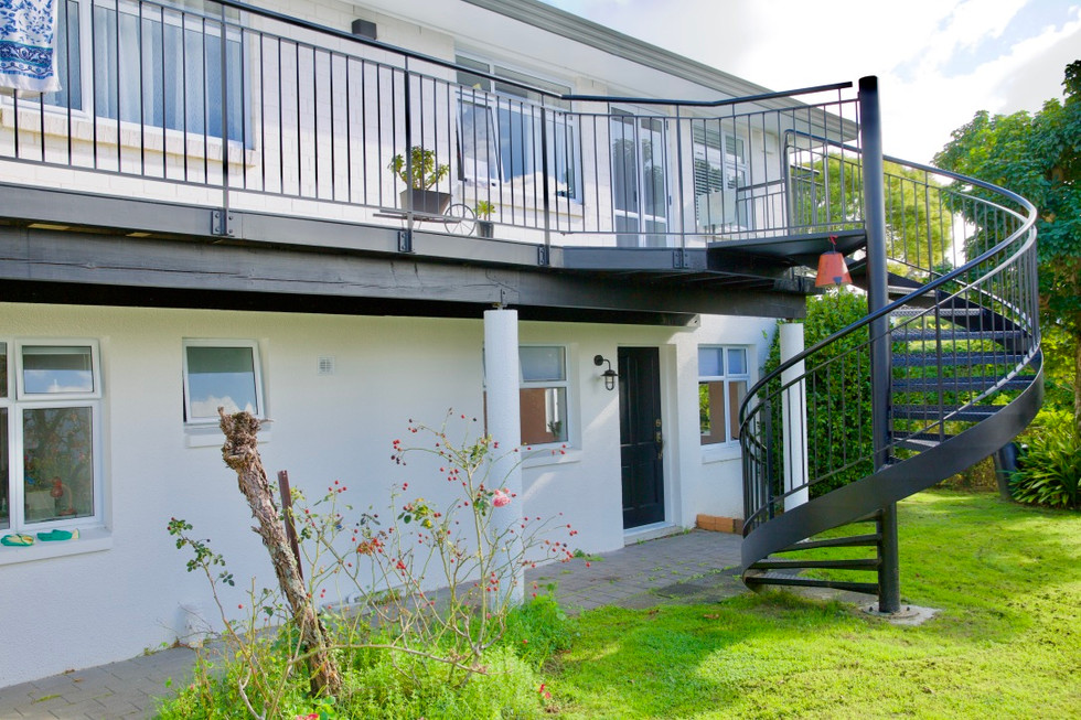 Spiral staircase designed as architectural feature in backyard of this Auckland home.