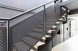 Perforated steel balustrade gives this staircase a more modern look and design.