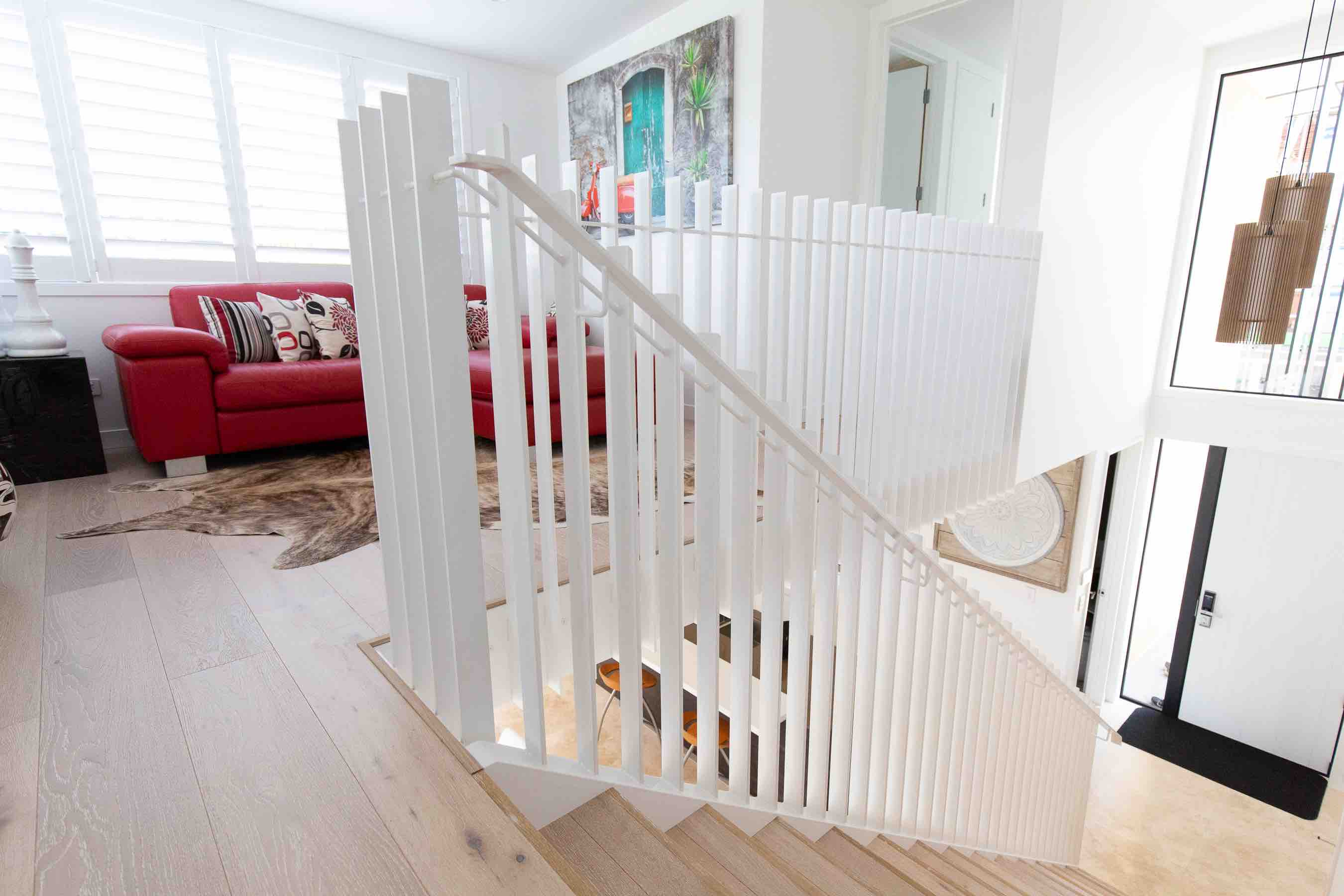Contemporary staircase design with a metal handrail and balustrade.