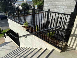 Metal balustrades powder coated black matte on apartment entryway stairs