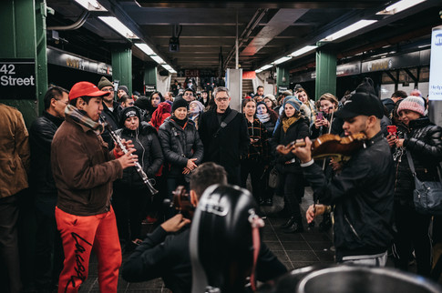 Street musicians Duoyi Xi, David Hincapie and Wuilly May play for a crowd at 42nd Street-Times Square Subway Station, New York City, November 13, 2019.