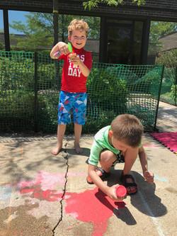 boy painting sidewalk