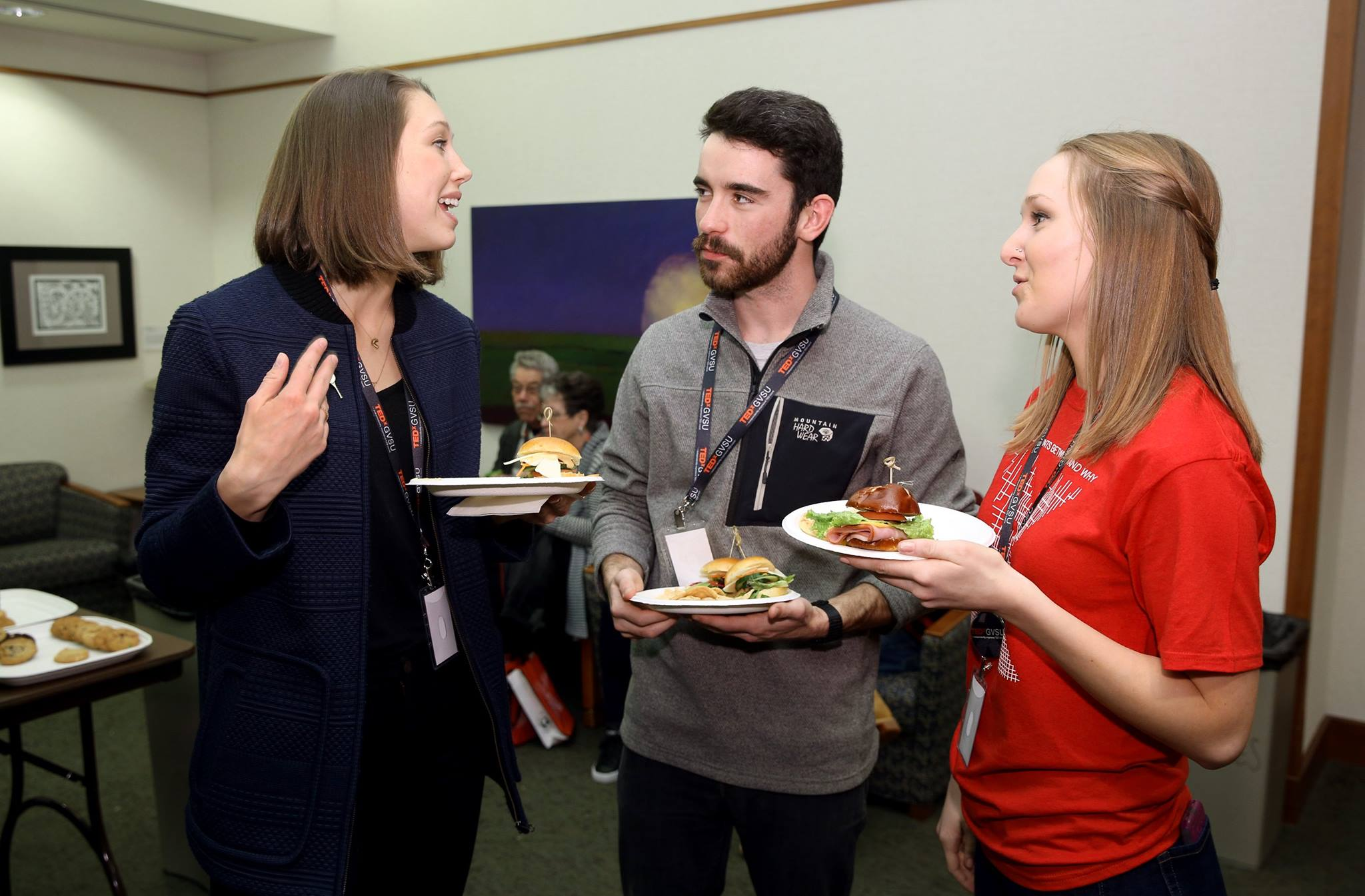 TedXGVSU attendees chat with a volunteer.