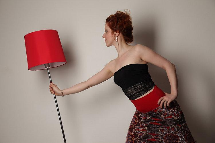 Jeune femme portant jupe de tango ceinture rouge et imprimé tribal, haut noir detell, lampe rouge