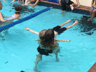Swim instructor helping kid