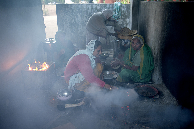 Women with infants, cooking indoors.