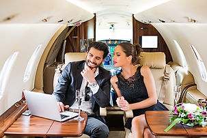 Couple looking at laptop inside jet