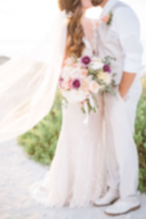 Bride and groom on island beach with romantic wedding bouquet