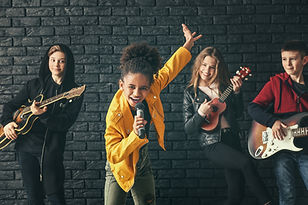 Band of teenage musicians playing agains