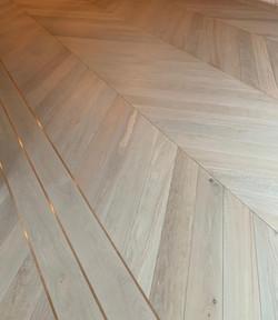Oversized chevron wood floor with bronze