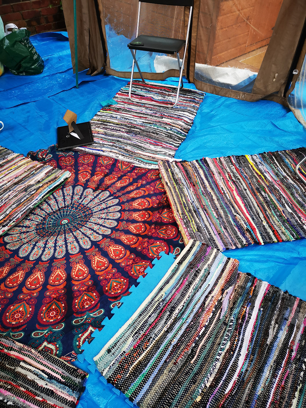 Beautiful but soggy rag rugs on tarpaulin
