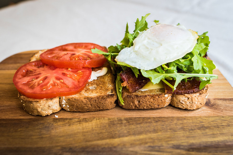 Header section backgroung image on hash restaurant home page. image of toast with bacon and eggs, tomato lettuce on a cutting board