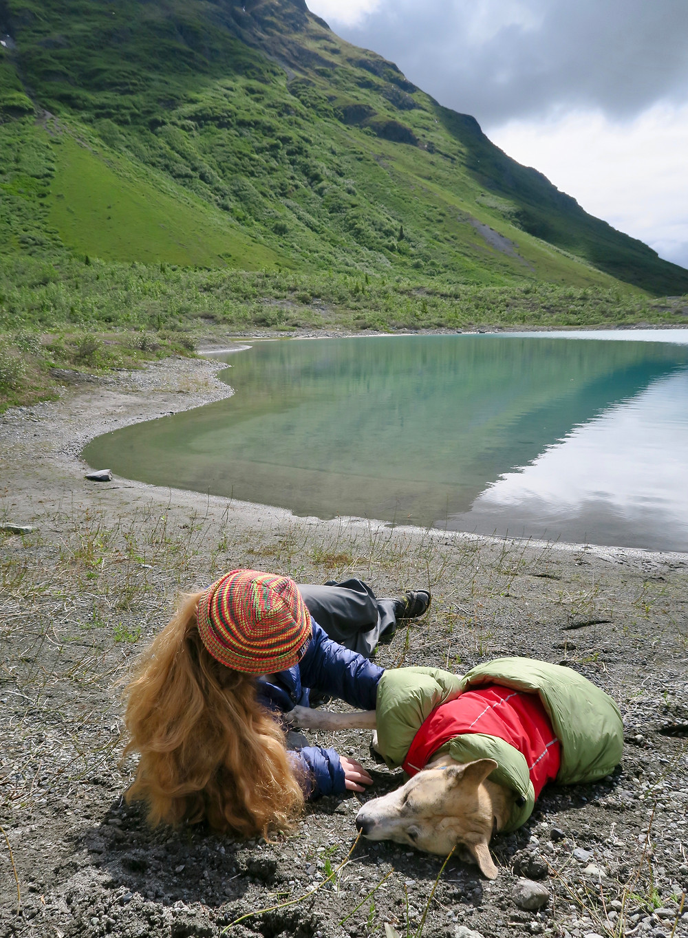 A young woman with long blond hair lays on the ground in sunshine by the edge of a lake petting a blond dog.