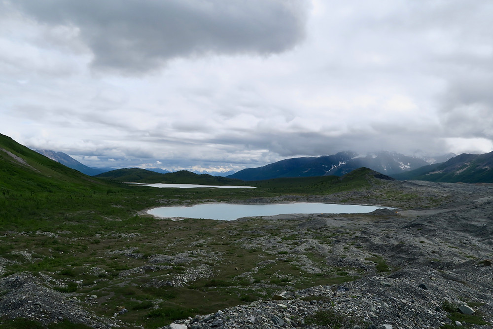 A view from above of two small lakes, dark mountains in the distance, and clouds overhead.