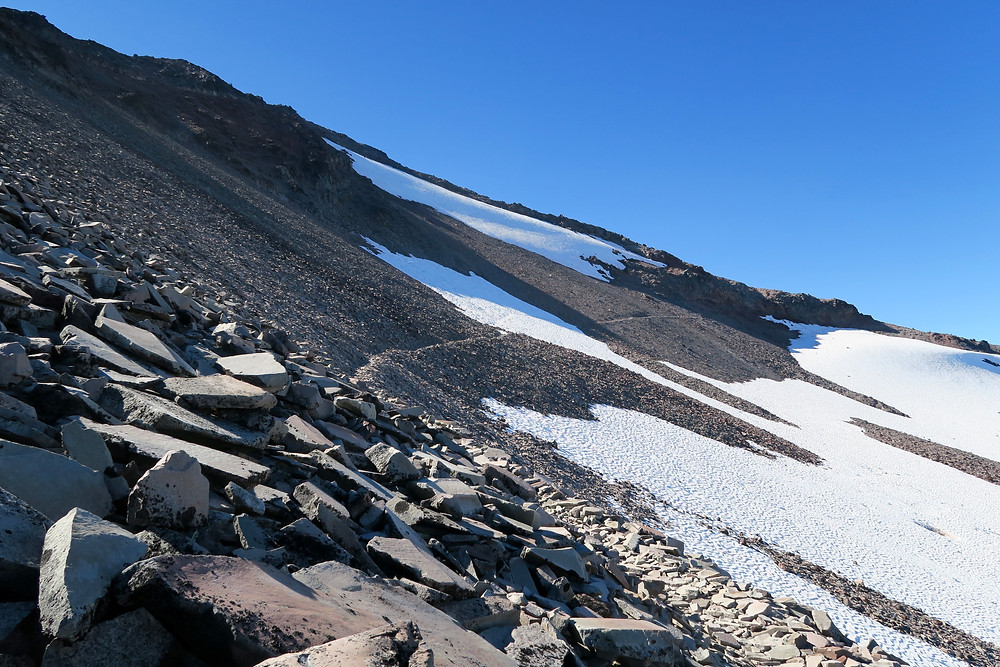 A steep embankment of loose rocks with the thin line of a trail reaching into the distance across snow.