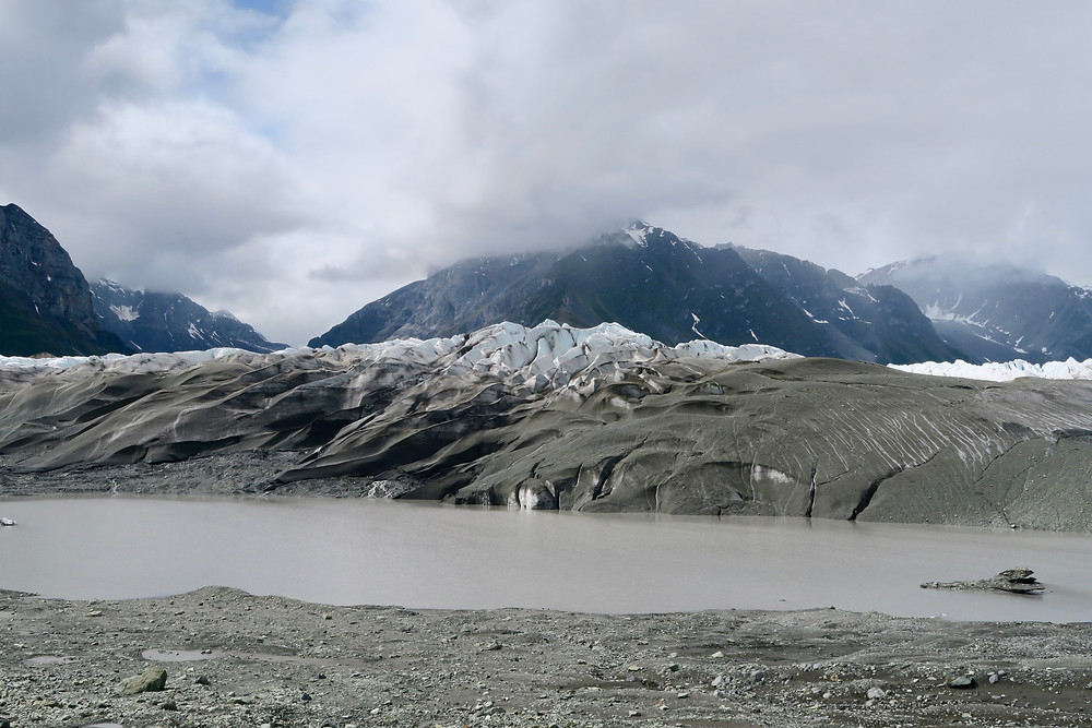 Sharp and steep ridges of ice with gravel at the lower edges, a gray pond in the foreground, and dark mountains in the background.