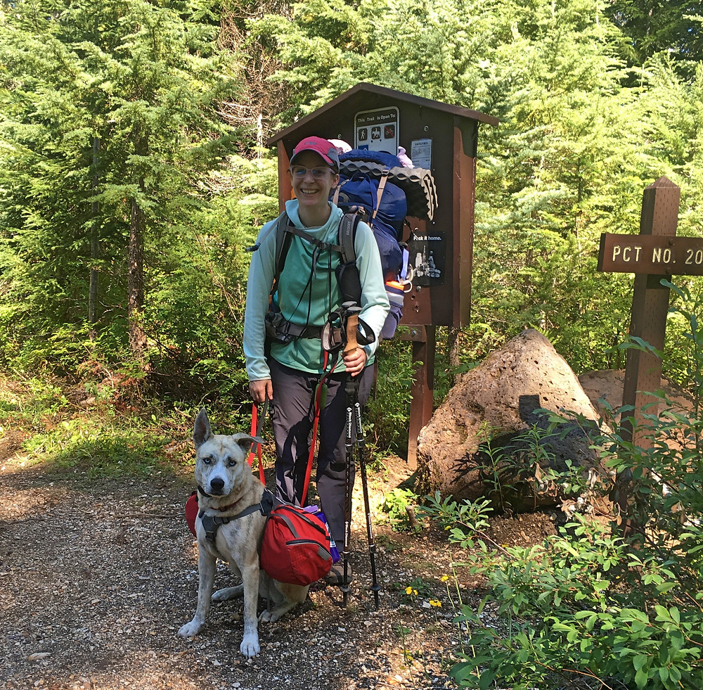 A young and thin white person is standing at a trailhead wearing a bulging blue pack and holding hiking poles. A blond dog wearing a red pack sits at her feet.