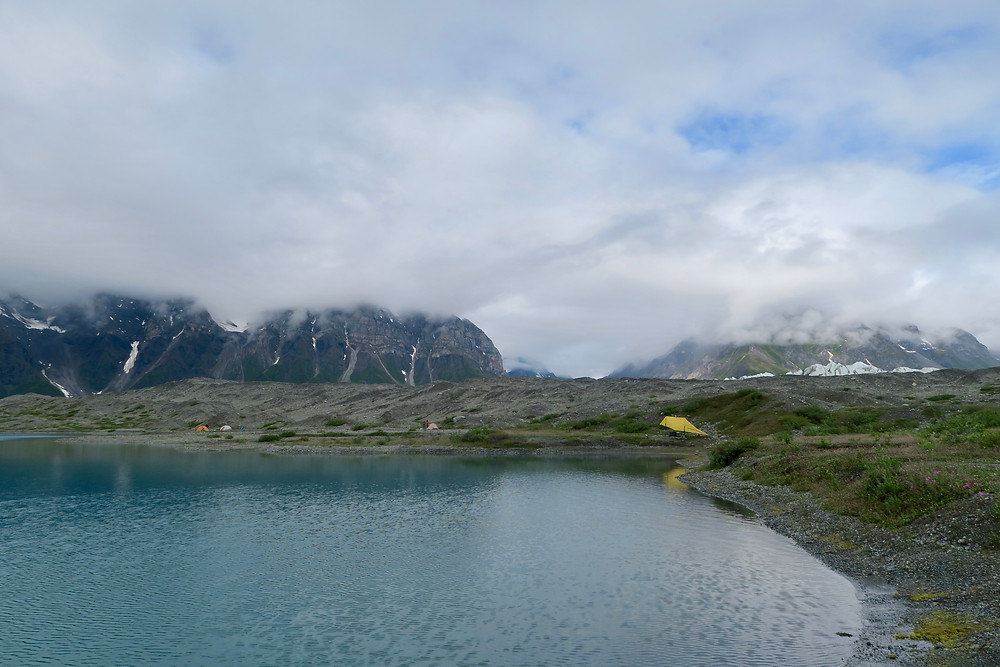 A turquoise lake with low-hanging clouds obscuring snowy mountains.