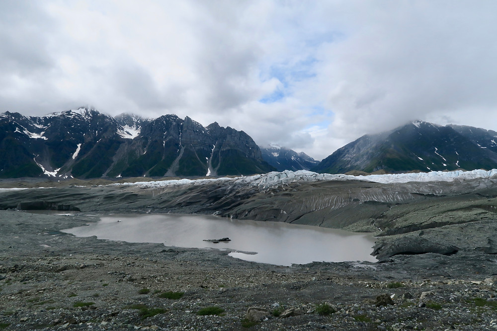 A dirty brown pond in front of gray and white ice in jagged peaks, steep rocky mountains in the distance and gray clouds overhead.
