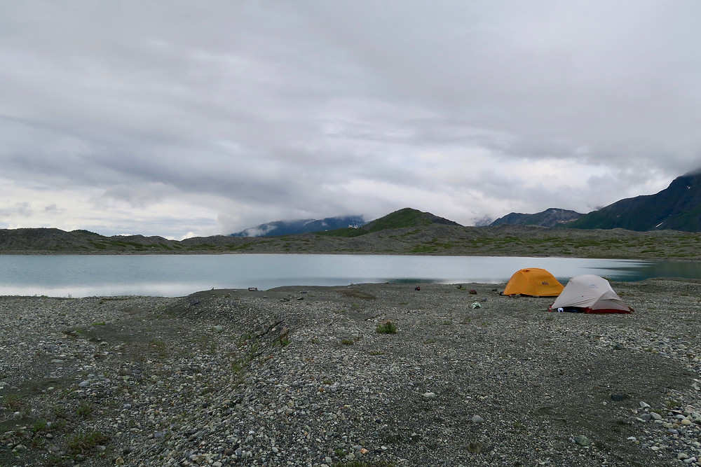 Two tents sit on gray rocks and gravel near a lake reflecting dark storm clouds.