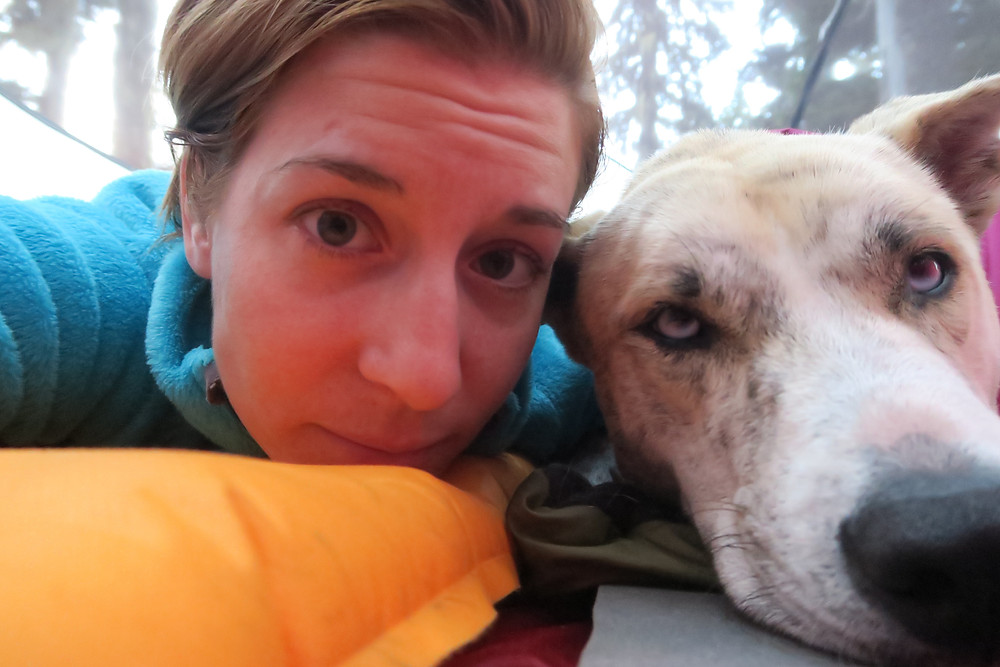 A young woman with short light brown hair looks at the camera with her head next to the face of a blond dog.