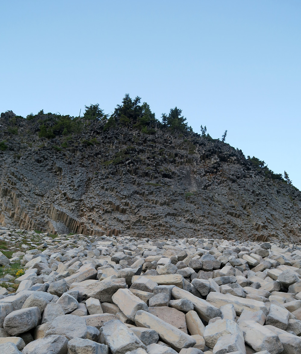 A mountain side is covered in hexagonal columns of basalt rock sticking up from the ground.