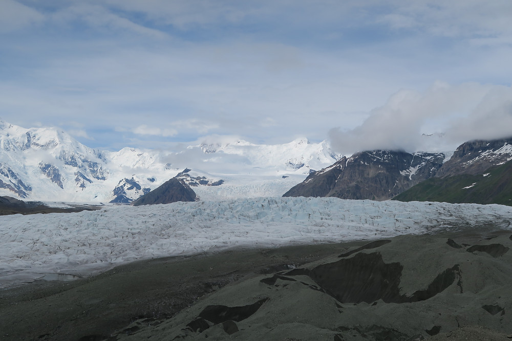 A blue sky overhead with sparse white clouds, white snowy mountains in the distance, blue ice cascading down to a light blue and white river of ice edged by dark brown rocks.