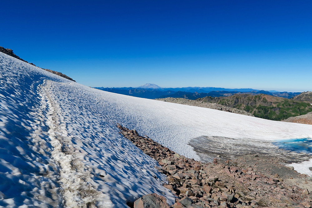 A steep snowy bank of rocks with a path of footsteps.
