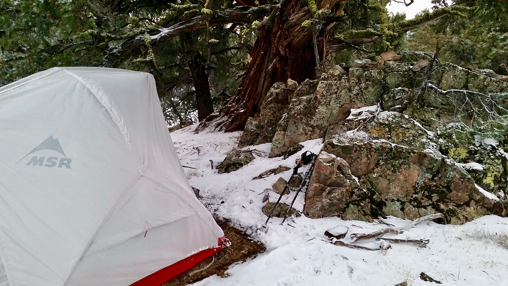 A tent with a gray raincover is surrounded by rocks, pine forest, and an inch of snow on the ground.