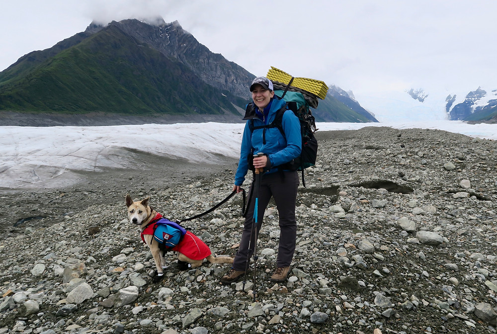 A woman wearing a blue coat and a large pack stands next to a glacier with her dog sitting at her feet.
