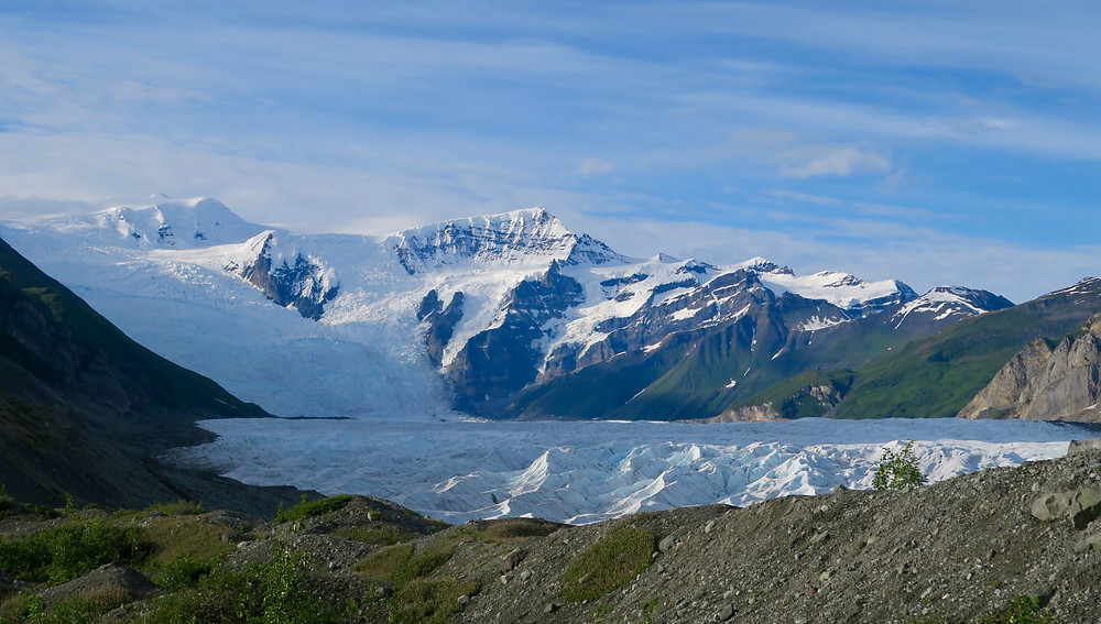 A blue and white glacier flows down a snow-capped mountain and into the valley below.