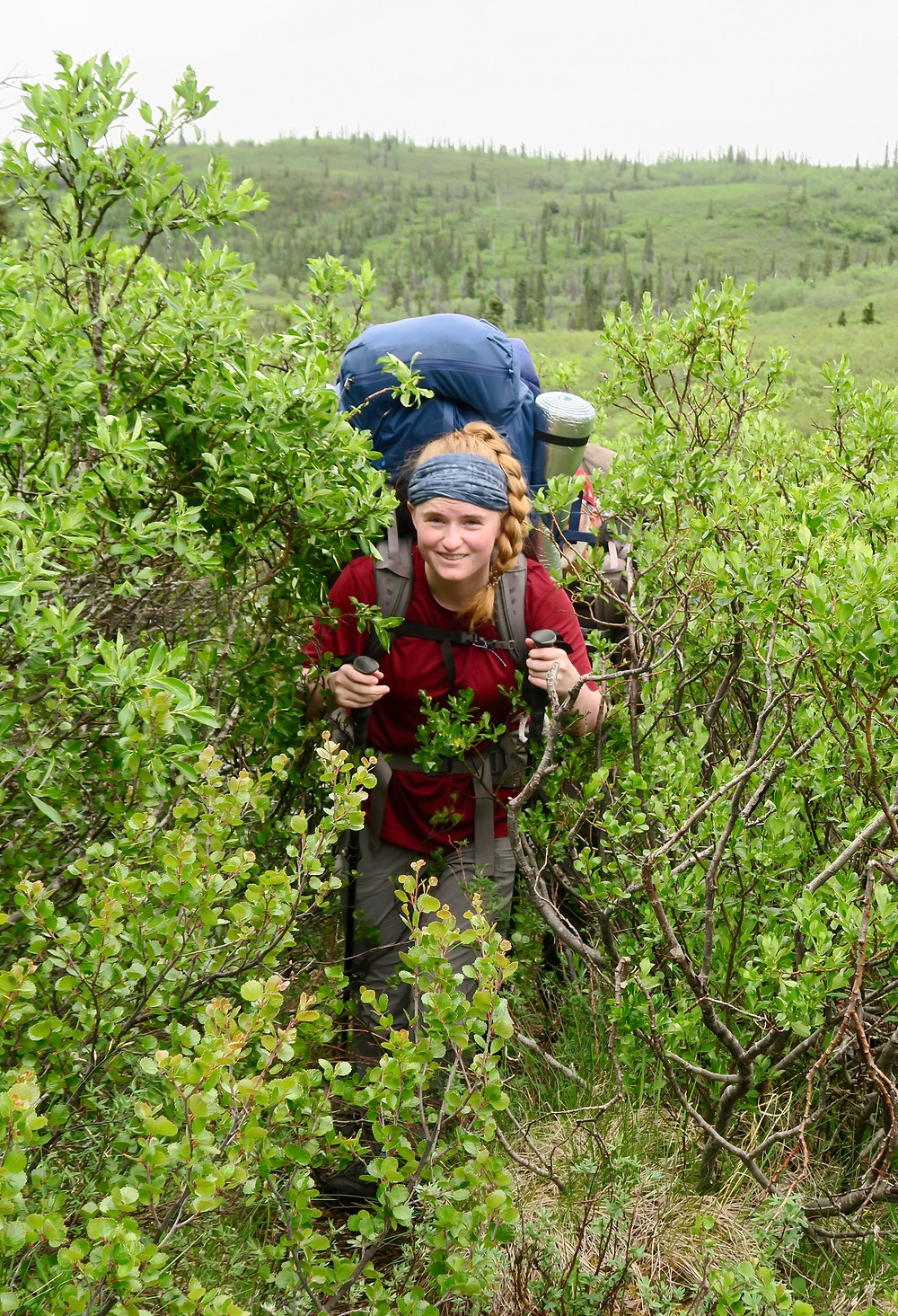 A young white woman wearing a large blue backpack and carrying hiking poles smiles at the camera. She is surrounded by seven foot trees and green plants.