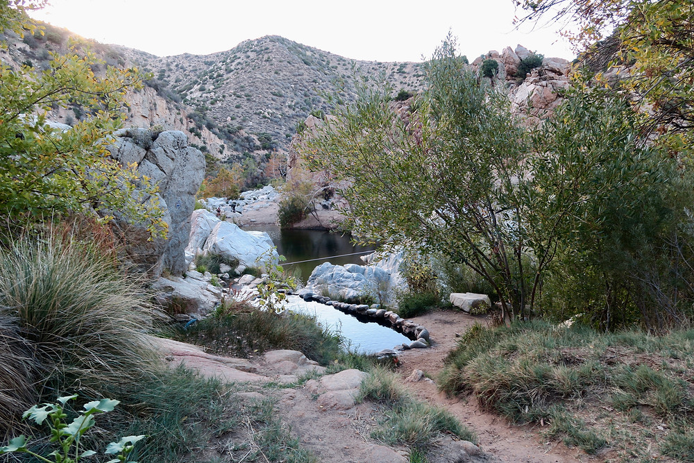Small natural pools edged in rocks lay just above the wide creek, tucked in the valley of the shrub-covered hills.