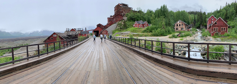 A panoramic view of a wooden bridge leading to a mill town of red buildings on a hill. A waterfall leads under the bridge on the right side.