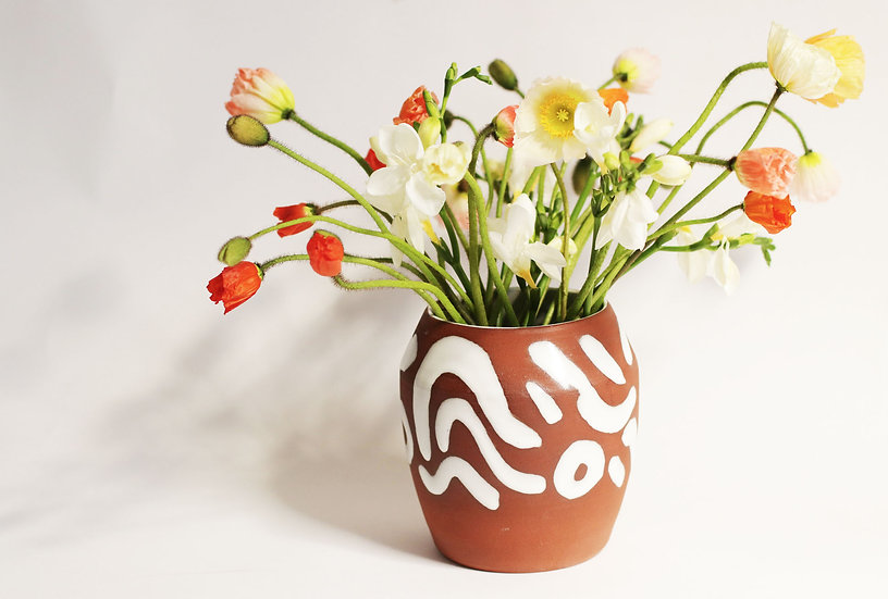 Terracotta vase with white squiggles