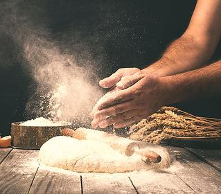 Man preparing bread dough on wooden tabl