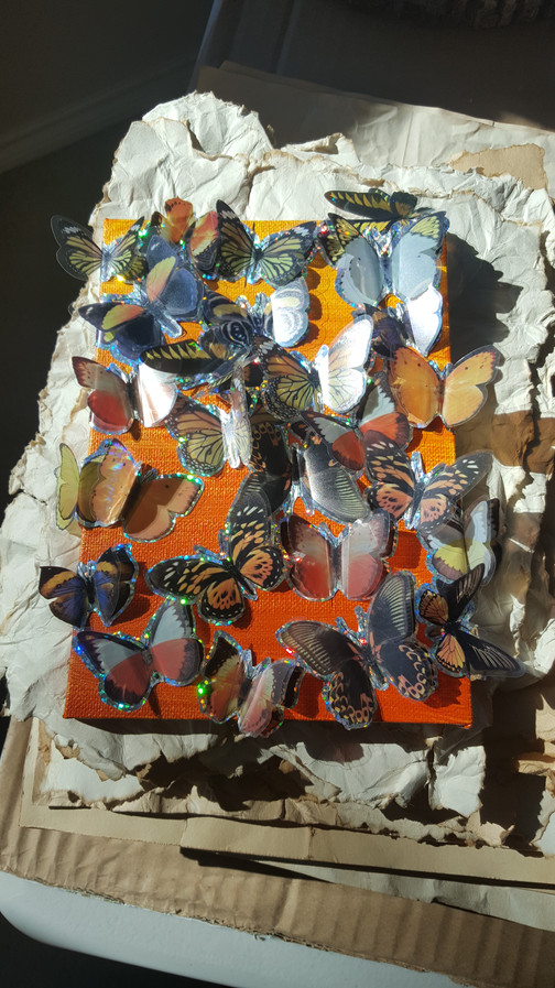 I started by painting both canvases a sunset gradient of orange to yellow.  Then, I covered the first canvas in as many butterfly stickers as I could fit on it. The many.