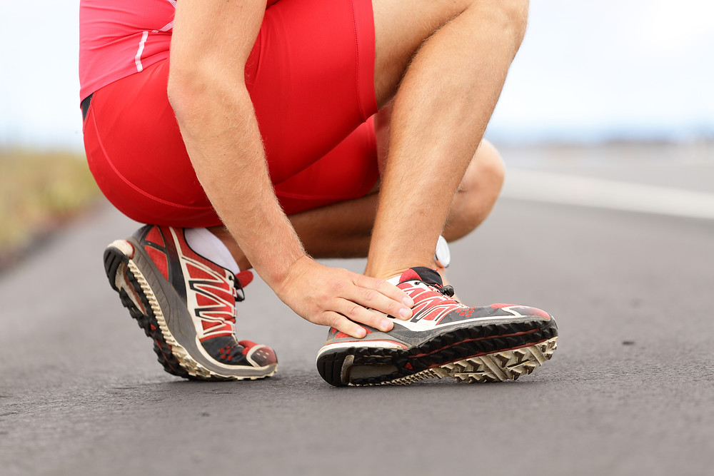 Broken twisted ankle - running sport injury. Male runner touching foot in pain d