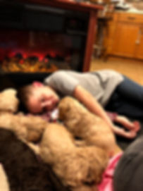 child snugging with puppies laying on the floor