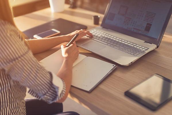 Female designer using laptop, sketching