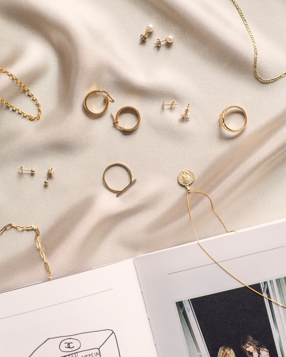 A flat lay image of a variety of gold jewellery on a silk background with a book.