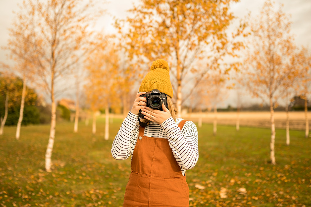 a female photographer holding a camera up to her face, standing amongst silver birch