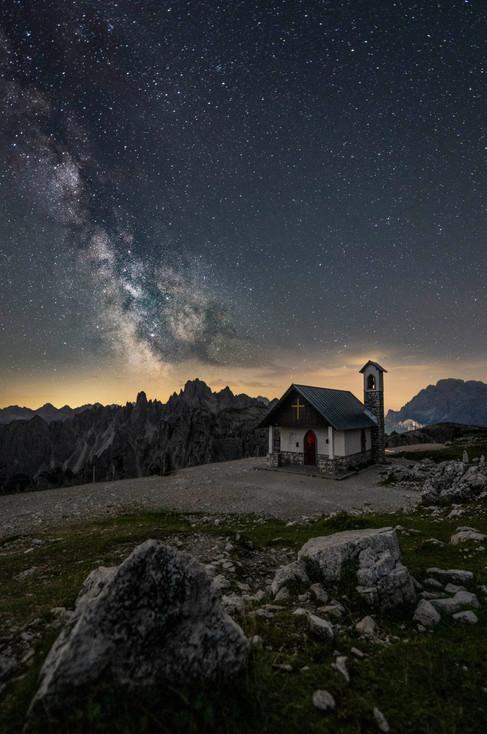 Die Milchstraße über einer kleinen Kapelle an den Drei Zinnen
